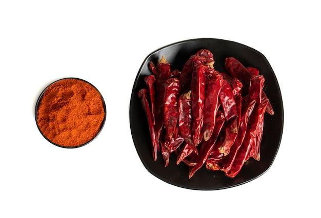 Pimentas vermelhas secas com pimenta em pó no fundo branco