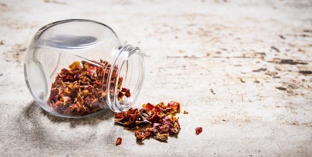 Pimentas vermelhas secas em frasco na mesa rústica.
