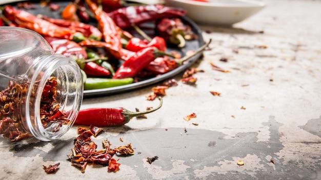 Pimentas vermelhas secas na bandeja e no frasco na mesa rústica.