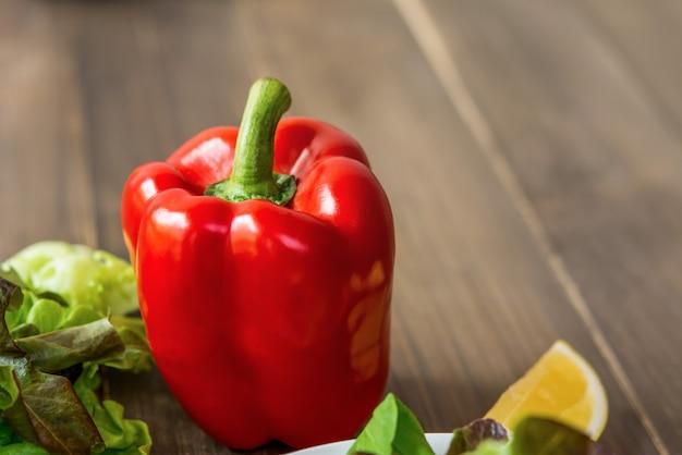 Pimento vermelho colorido com vegetais verdes na mesa de madeira