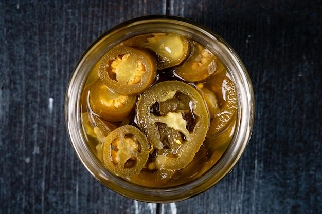 Pimentões caseiros picantes de jalapeno marinados e cortados em uma tigela de vidro sobre uma mesa de madeira escura