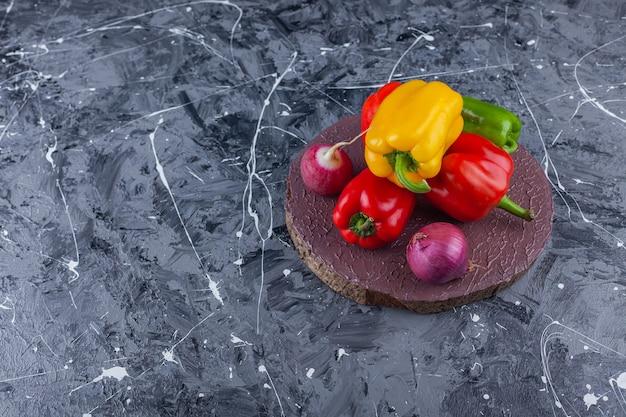 Pimentões coloridos, cebola e rabanete vermelho na peça de madeira.