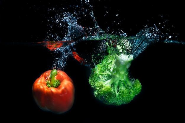 Pimentões e vegetais frescos da paprika que espirram no respingo claro da água