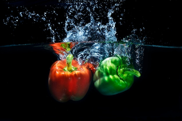 Pimentões frescos da paprika que espirram no respingo claro da água