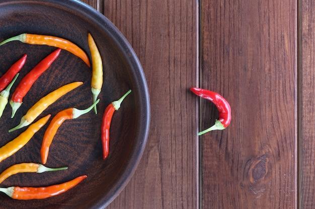 Pimentões grelhados vermelhos e amarelos em casa, no fogão em prato de argila marrom em close-up de fundo de madeira