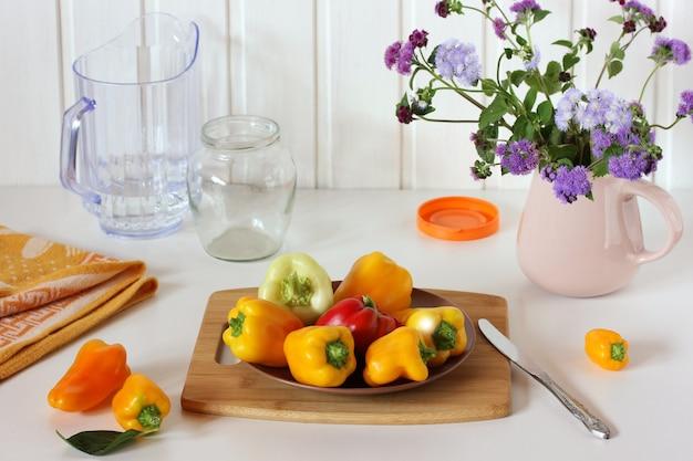 Pimentões maduros e um buquê de ageratum em uma jarra de flores e vegetais em uma mesa branca