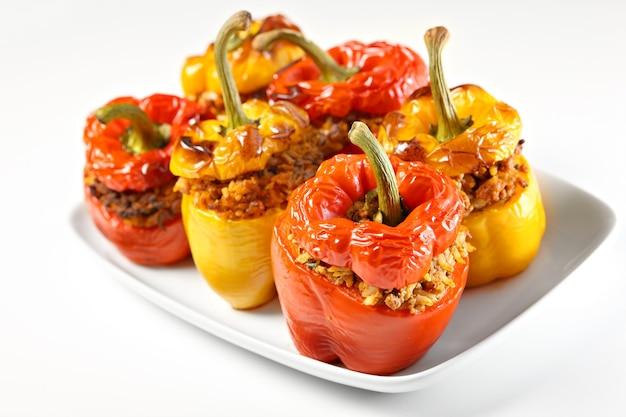 Pimentões recheados vermelhos e amarelos assados e servidos em um prato branco