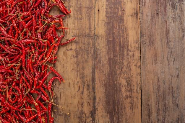 Pimentões secos vermelhos que são empilhados na prancha.