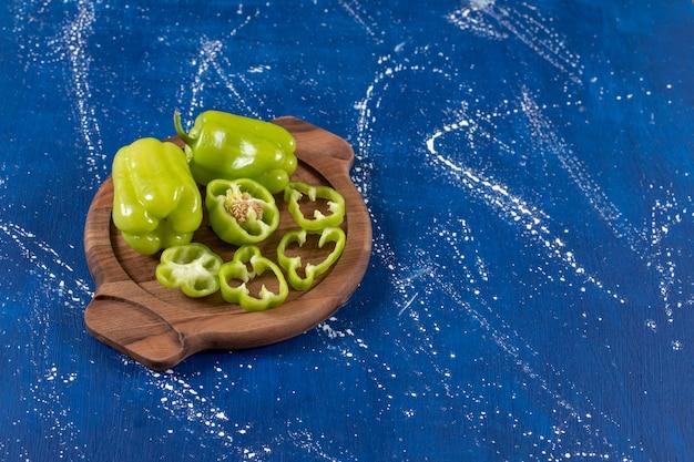 Pimentões verdes e anéis na placa de madeira na superfície de mármore