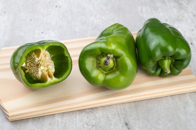 Pimentões verdes e vegetais cortados sobre uma placa de madeira.