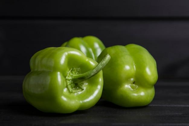 Pimentões verdes inteiros colocados na mesa de madeira escura. foto de alta qualidade