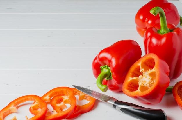 Pimentões vermelhos maduros e uma faca de cozinha