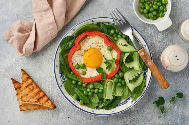 Pimentões vermelhos recheados com ovos, folhas de espinafre, ervilhas e microgreens em um prato de café da manhã no fundo da mesa cinza claro. vista do topo.
