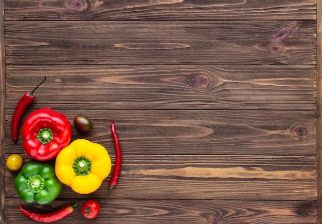 Pimentões vermelhos verdes e amarelos, pimentão e tomate cereja em fundo de madeira