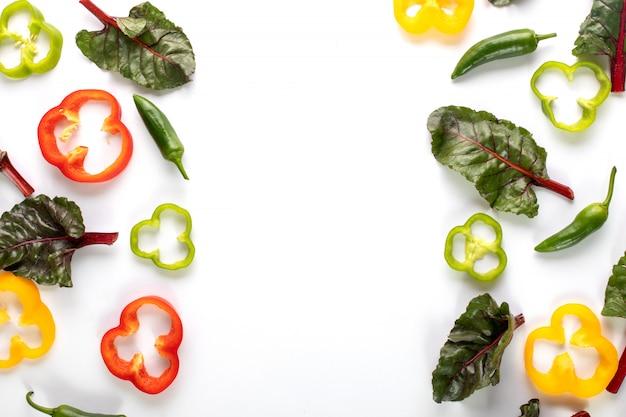 Pimentos coloridos frescos pimentões maduros e fatiados, juntamente com pimenta verde picante e folhas em fundo escuro