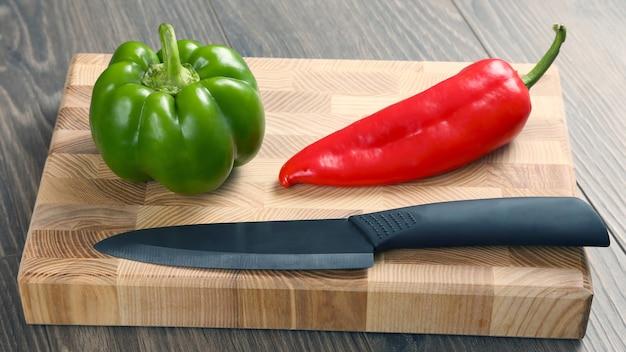 Pimentos doces com uma faca de cerâmica em uma placa de madeira. comida crua para cozinhar