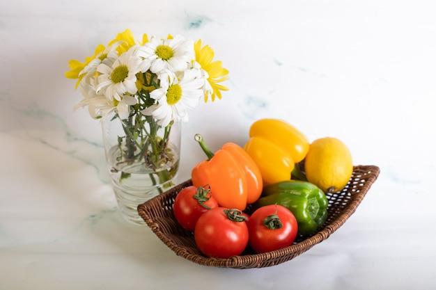 Pimentos e tomates no prato sobre o mármore