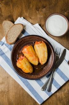 Pimentos recheados com arroz e carne picada guisado em tomate, pão de centeio. comida rústica.