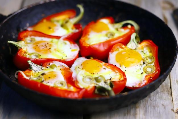 Pimentos vermelhos com ovo, assados em uma panela.