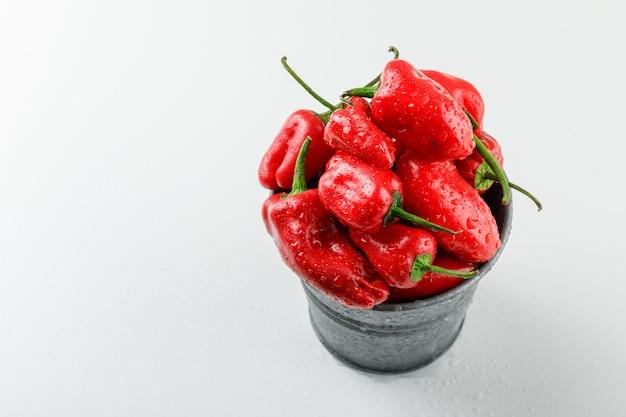 Pimentos vermelhos em um mini balde vista de alto ângulo em uma parede branca