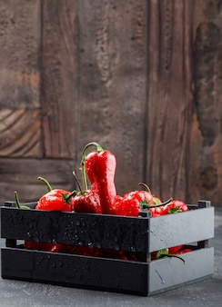 Pimentos vermelhos em uma vista lateral de caixa de madeira na parede de azulejos cinza e pedra