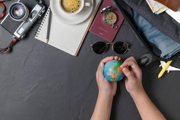 Pin no mapa do mundo e prepare uma mala, câmera vintage, caderno, passaporte, mapa e café quente em fundo preto. conceito de viagens