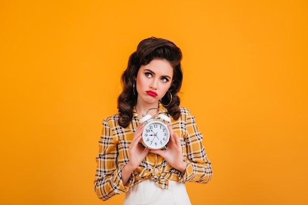 Pin-up triste segurando o relógio. foto de estúdio de pensativa jovem em camisa quadriculada amarela.