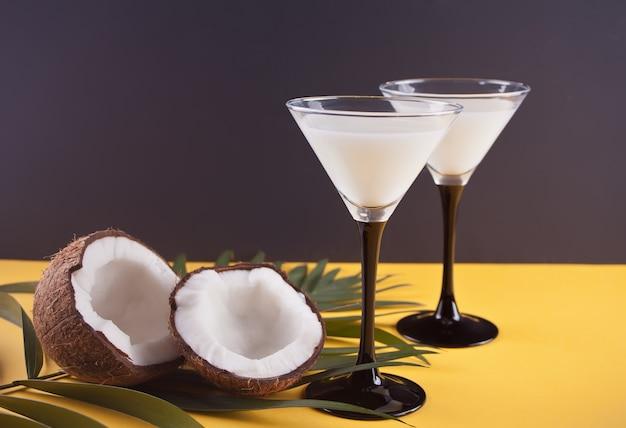 Pina colada cocktail na mesa amarela com folha de palmeira e coco no fundo