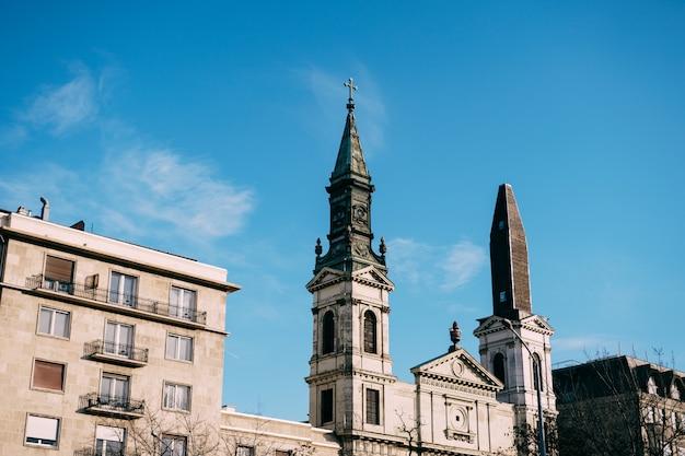 Pináculos de uma bela basílica antiga em budapeste contra um céu azul com nuvens brancas