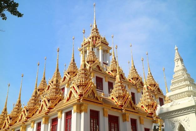 Pináculos dourados do histórico castelo de ferro loha prasat dentro do templo wat ratchanatdaram em bangkok, tailândia