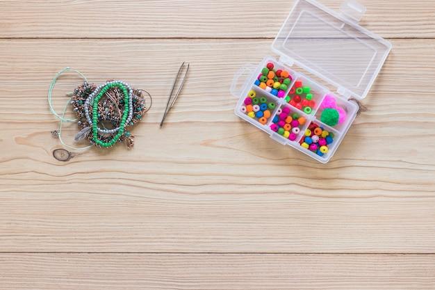 Pinça; pulseira e miçangas na caixa de plástico branca na mesa de madeira