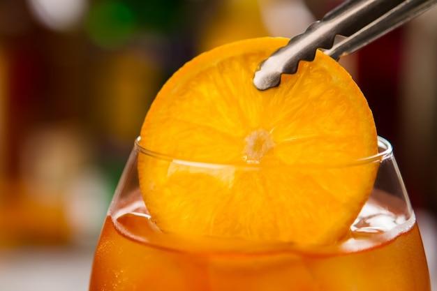 Pinças com rodelas de laranja. copo cheio de bebida. bebida alcoólica fresca. você já experimentou aperol spritz.