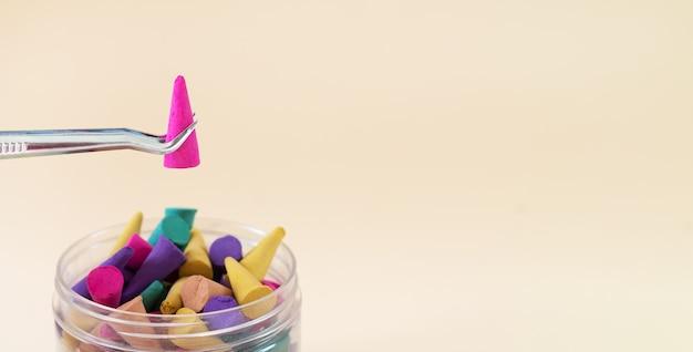 Pinças de metal segurando o cone de incenso aromático sobre o frasco com cones coloridos. banner com espaço de cópia