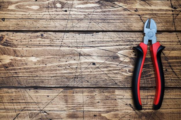 Pinças dos alicates no fundo de madeira com espaço da cópia. ferramentas de reparação.
