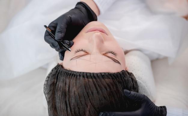 Pinças master de maquiagem permanente puxando as sobrancelhas da garota modelo em preparação para o microblading