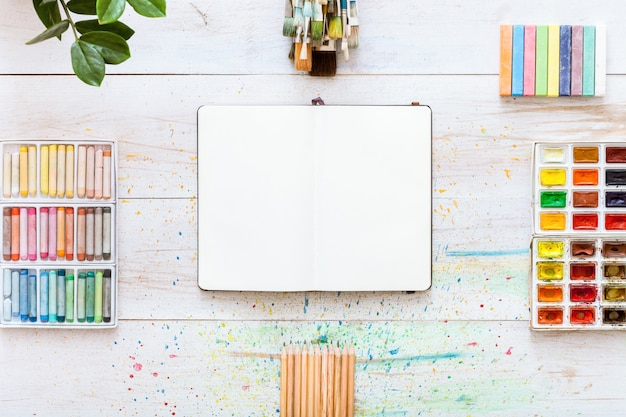 Pincéis, aquarelas de paintbox, caderno aberto sobre fundo branco de madeira