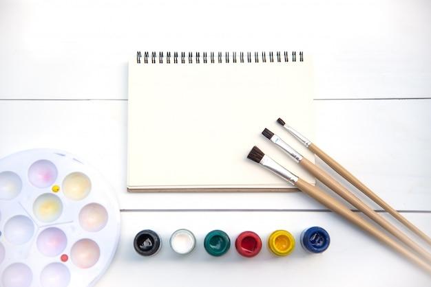 Pincéis artísticos, colocados em um livro de desenho com aquarelas.