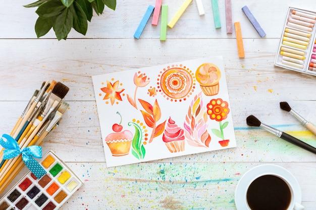 Pincéis com aquarelas e mock-se papel em branco na mesa de madeira branca