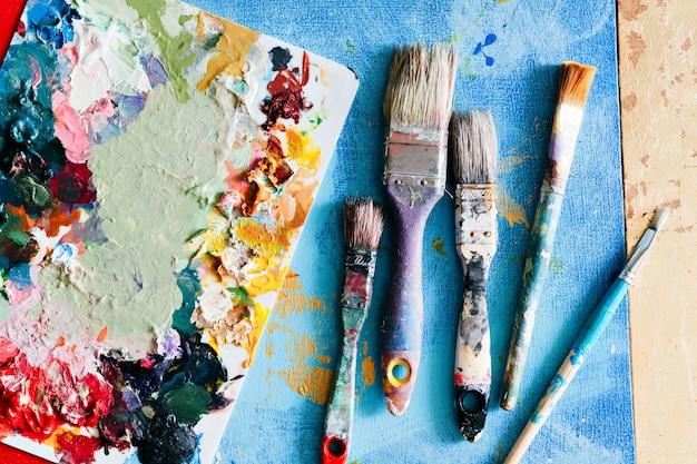 Pincéis com paleta na composição criativa. elemento colorido