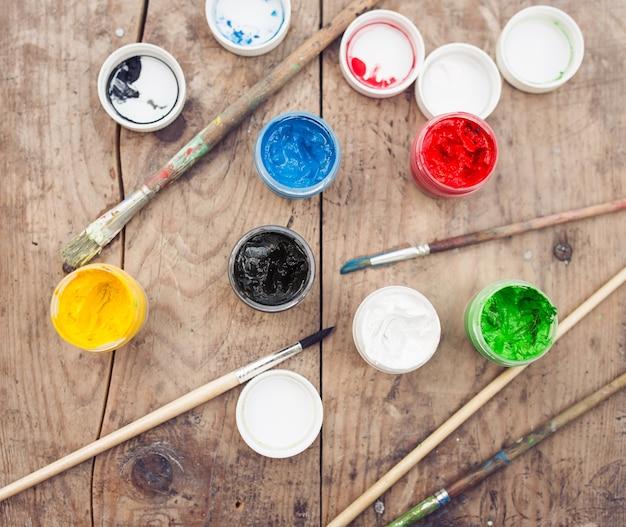 Pincéis com tintas coloridas em fundo de madeira velho