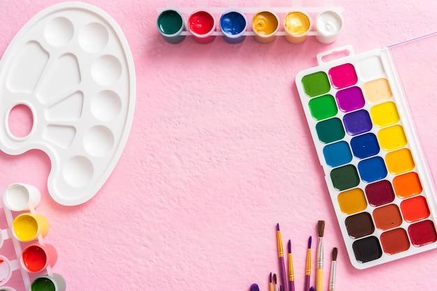 Pincéis com tintas em um fundo rosa. copie o espaço.