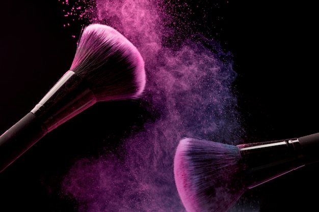 Pincéis cosméticos e pó de maquiagem em fundo escuro