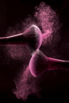 Pincéis cosméticos na névoa rosa de pó em fundo escuro