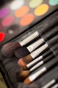 Pincéis cosméticos. sombras de olhos multicoloridas com escova de cosméticos
