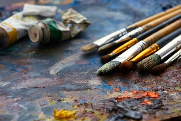 Pincéis de arte e tintas a óleo em uma paleta close-up