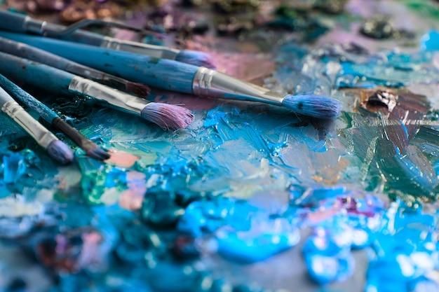 Pincéis de artistas e tintas a óleo na paleta de madeira