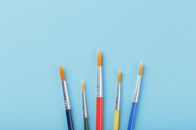 Pincéis de cores diferentes para desenho, criatividade e arte sobre um fundo azul.