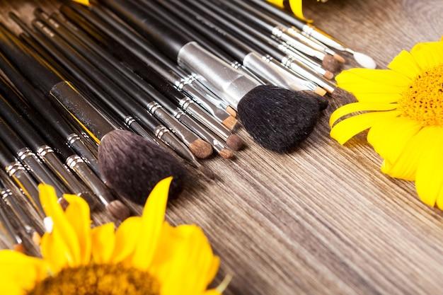 Pincéis de maquiagem ao lado de flores em fundo de madeira