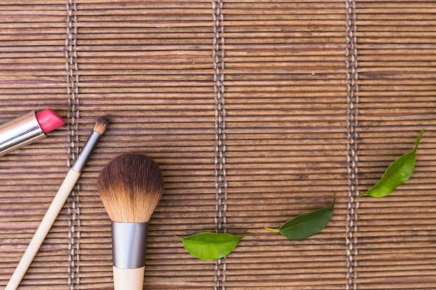 Pincéis de maquiagem com batom e folhas verdes no placemat