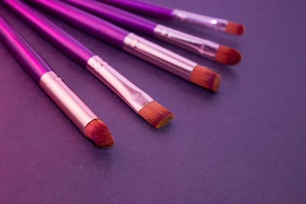 Pincéis de maquiagem com cabo roxo e cerdas laranja em fundo escuro, luz rosa